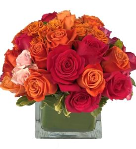 This design is HOT. Full of orange, hot pink, and pink roses and spray roses designed in a leaf wrapped glass cube that will heat up any space!